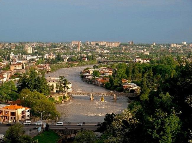 Город расположен на реке, среди высоких гор и густых лесов